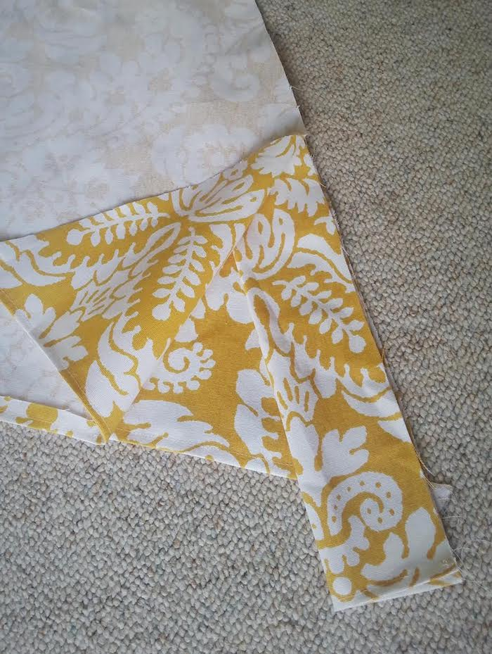 ein beiger teppich und ein gelbes dreieck aus einem gelben stoff mit vielen großen weißen blumen mit weißen blättern und ästen, eine diy anleitung, ein tipi zelt selber bauen