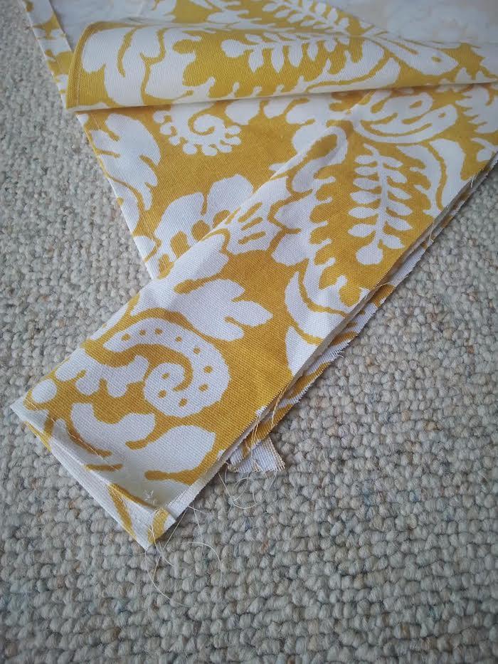 ein beiger teppich und ein gelber stoff mit vielen kleinen und großen weißen blumen und weißen blättern, ein tipi zelt selber bauen