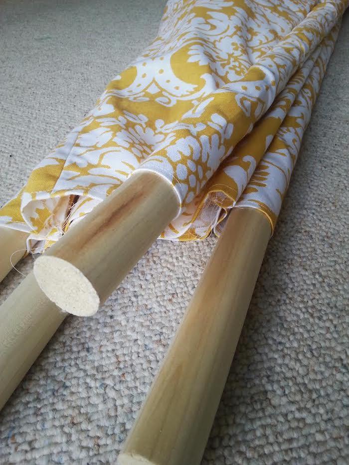 länge stöcke aus holz, ein grauer teppich und ein gelber stoff mit vielen weißen blumen mit weißen blättern, eine diy anleitung, ein tipi zelt selber bauen