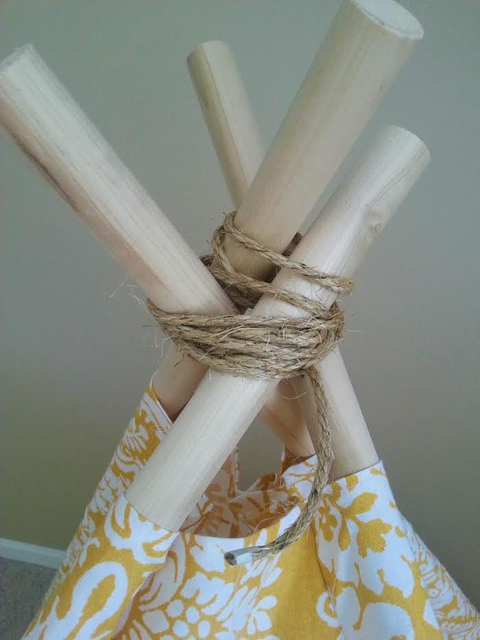 ein spielzelt tipi selber bauen, vier lange stöcke aus holz und eine schnur, ein gelber stoff mit weißen blumen und weißen blättern und ästen