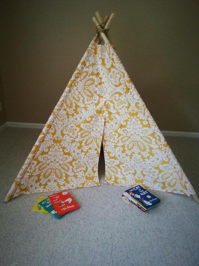 kleine grüne, gelbe, rote und blaue kinderbücher und ein grauer teppich, tipi kinderzelt mit stöcken aus holz und mit einem stoff mit weißen blumen und blättern