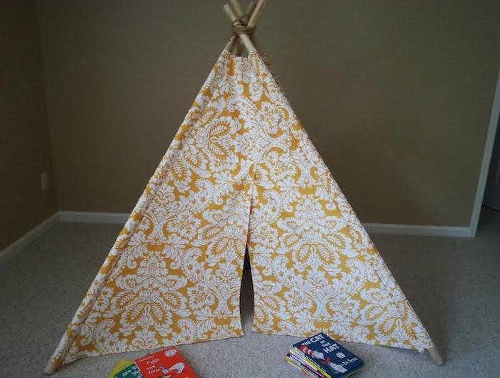 ein kleines gelbes tipi spielzelt mit einem gelben stoff mit vielen weißen blumen und weißen blättern, kleine rote und blaue kinderbücher