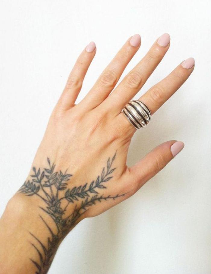 gänseblümchen tattoo, schwarz weiße tattoos, ein großer silberner ring am zeigefinger als ergänzung von dem tattoo
