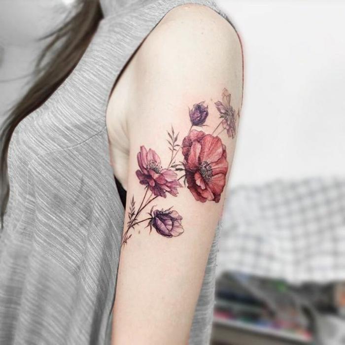 gänseblümchen tattoo in wasserfarben gemacht, fünf blumen an schulter mit farbe gestaltet, frau mit grauem top