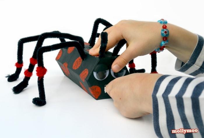 eine schwarze Spinne mit roten Flecken, das Kind spielt mit der Spinne, Basteln mit Klorollen