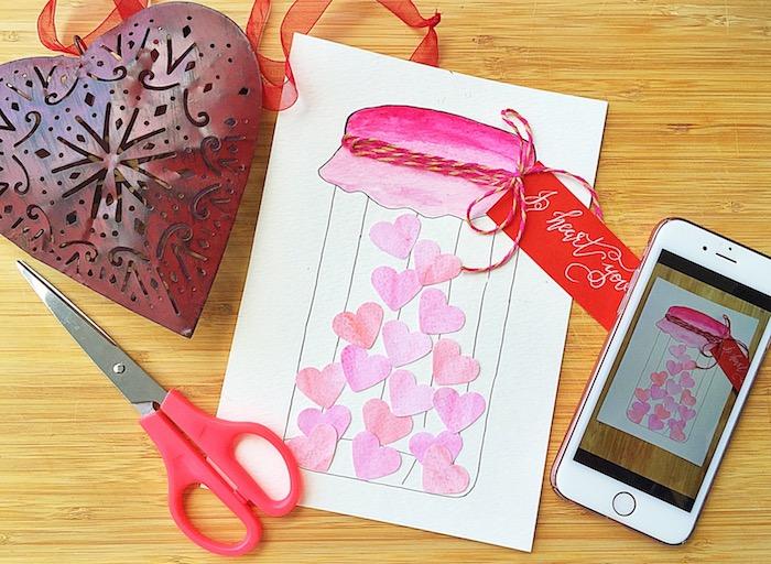 Selbstgemachte Hochzeitskarte, Einmachglas voll mit kleinen Herzen, Schere und Handy