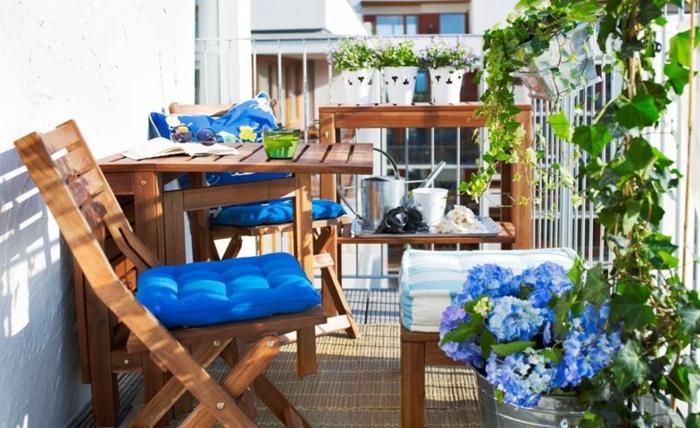klein aber elegant, balkon gestalten mit stil und geschmack, hölzerne stühle und kaffetisch mit blauen kissen bedeckt, blume blau, harmoniert mit der einrichtung des balkons