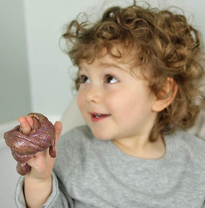 Brauner Schleim mit goldenem Glitter, süßes Kind mit braunen Haaren, mit Locken, graue Bluse