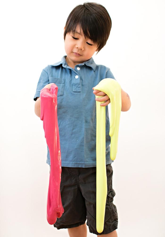 Roter und gelber Schleim mischen, süßes Kind mit schwarzen glatten Haaren, blaues T-Shirt und schwarze Hose