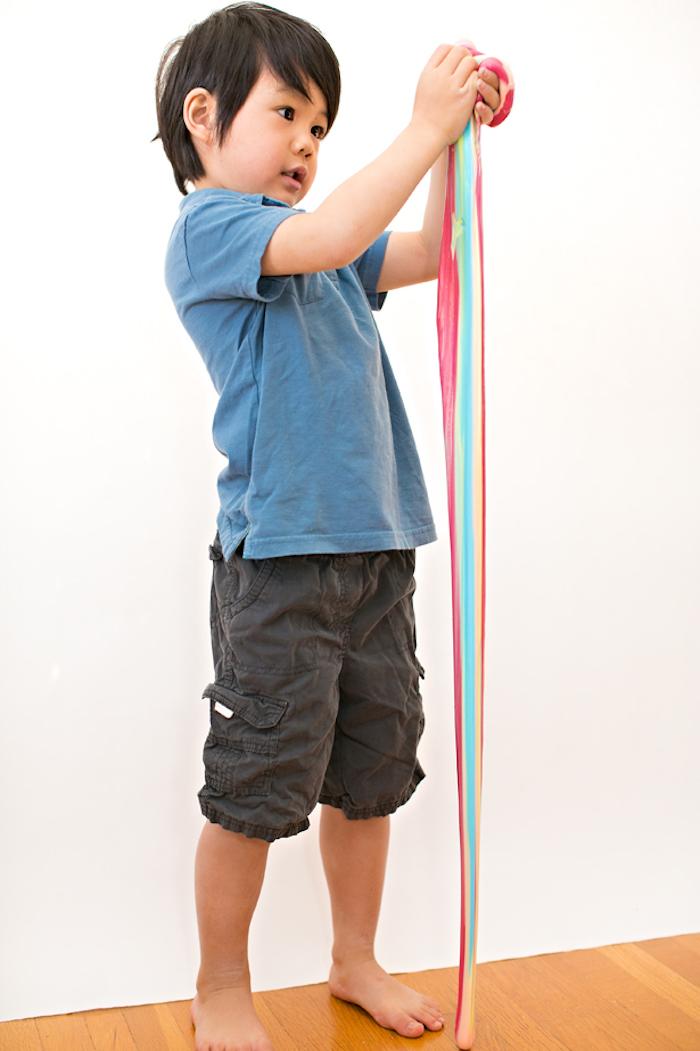 Süßes Kind spielt mit Regenbogen Schleim, verschiedene Farben, blaues Shirt und schwarze Hose