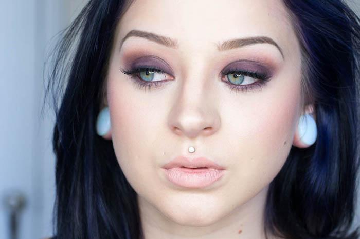 smokey eyes schminken, frau mit schwarzen haaren, ring über dem mund, make up in lila