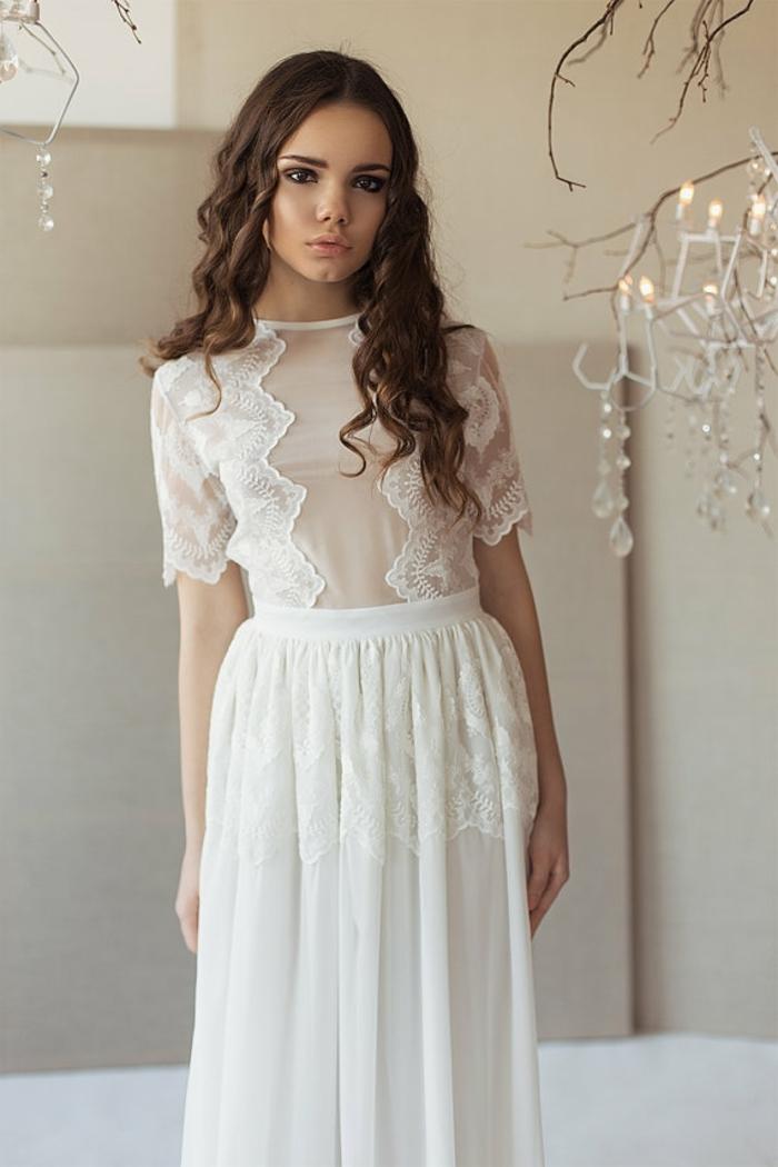 eine junge Braut mit lässigen Locken, weißes Brautkleid Boho Spitze