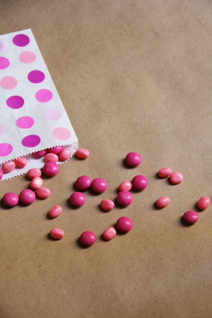 Papiertüten falten, rosa Papiertüte mit Punkten dekoriert, Tütte voller Bonbons