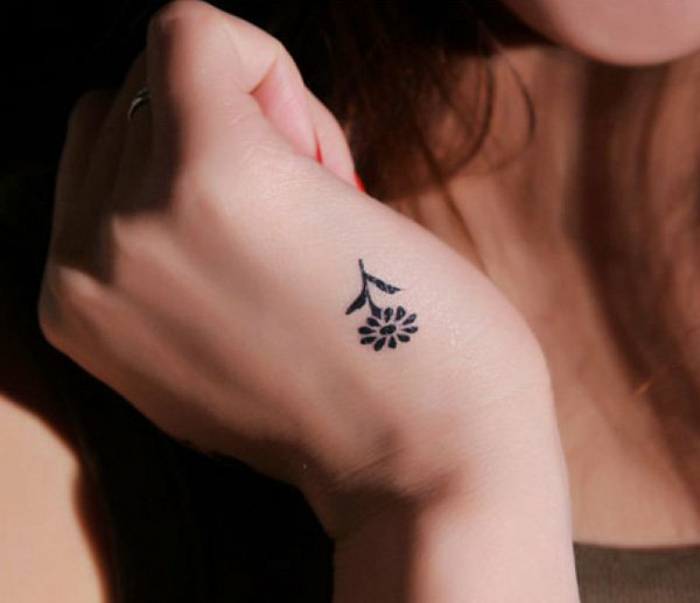 kleine und dezente blumen tattoo idee an der hand, gänseblümchen in schwarz, kleine tattoos