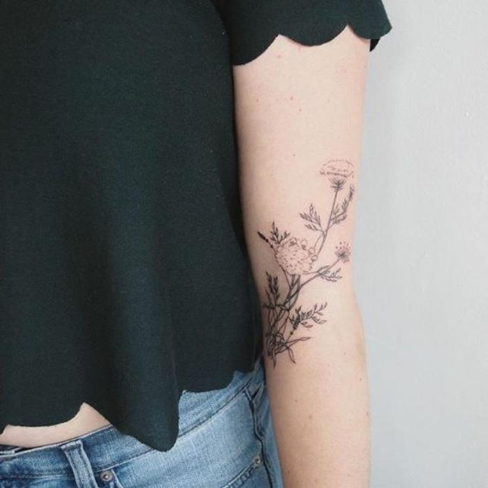 rosen tattoo schulter und arm, dezente zeichnung als tattoo am arm von einer frau, jeans und schwarzes top