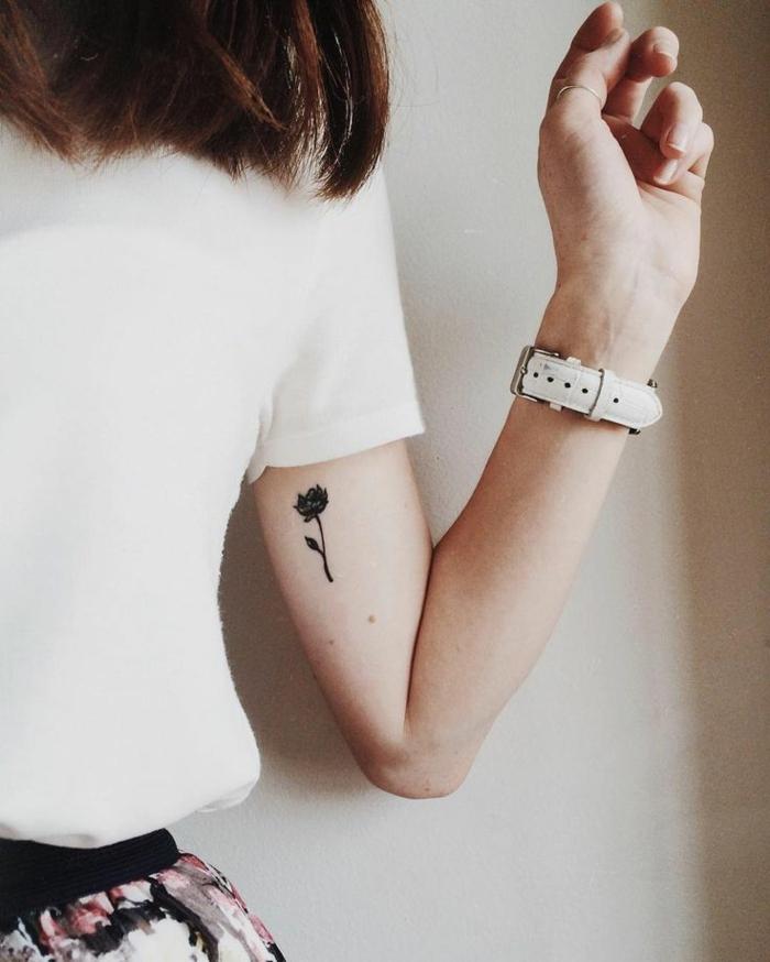rosen tattoo schulter und arm, frau mit mittellangen haaren, weißes shirt, weiße armbanduhr und kleines tattoo