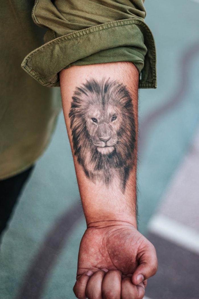 Schwarzes Tattoo am Unterarm, Löwen Tattoos für Männer, grünes Hemd