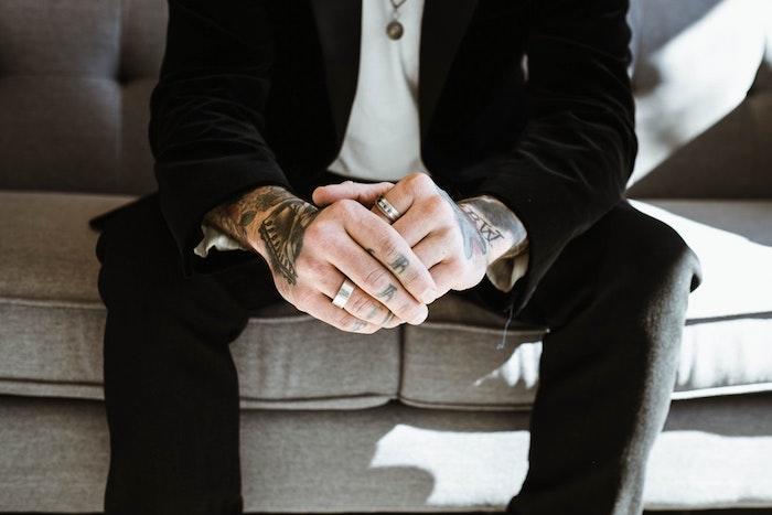 Tattoos an beiden Armen und an Fingern, Mann mit schwarzem Anzug und weißem Hemd