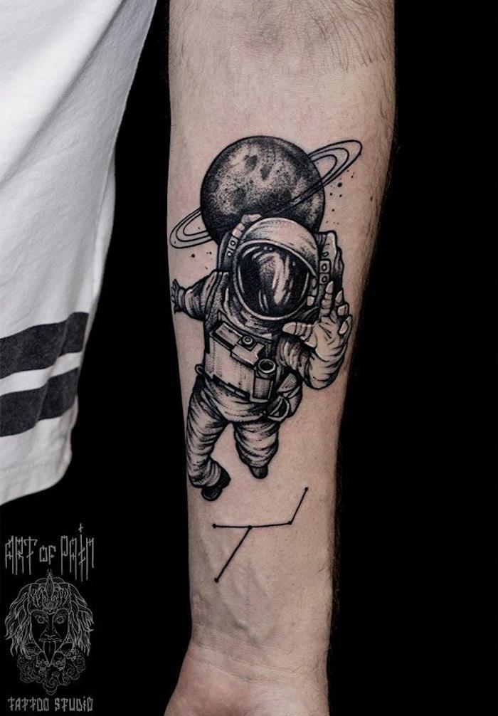 Schwarzes Tattoo am Unterarm, Kosmonaut und Saturn, große Tätowierung