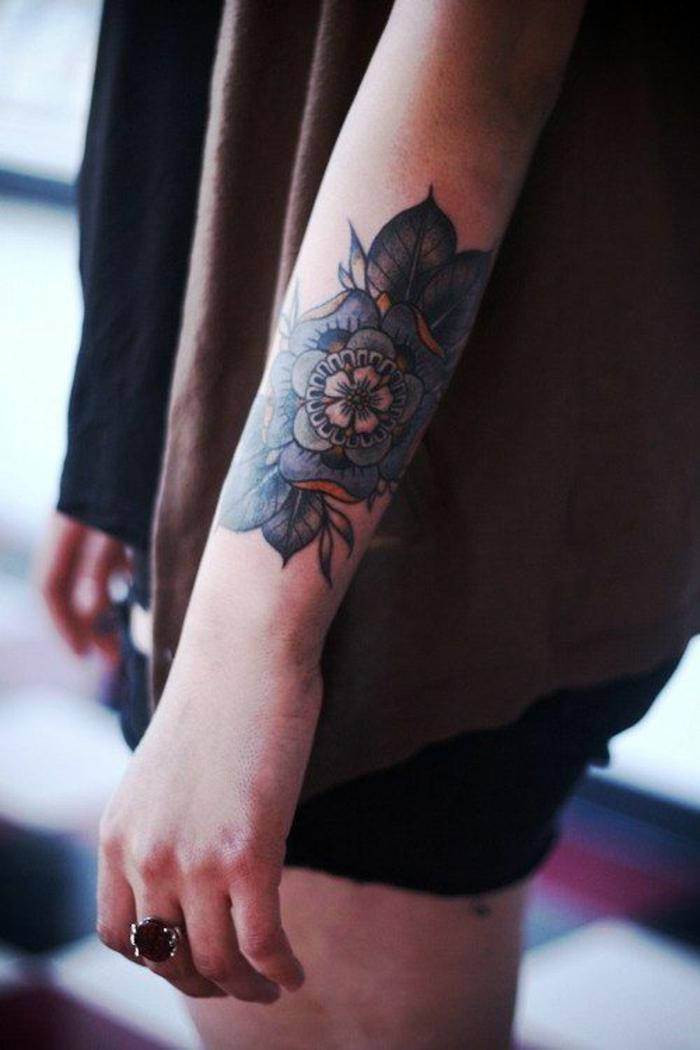 tattoos frauen schulter und arm, große blume in dunklen farben ausgefüllt, damenattoo