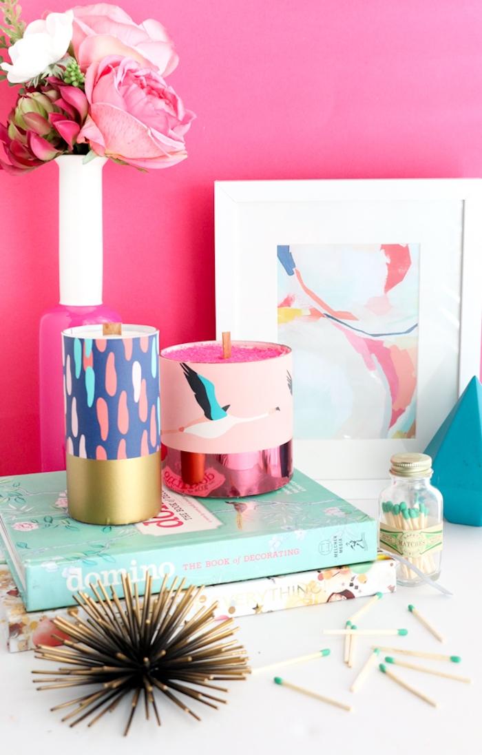 Selbstgemachte Kerze mit Storch, kleiner Blumenstrauß, zwei Bücher, rosa Wandfarbe
