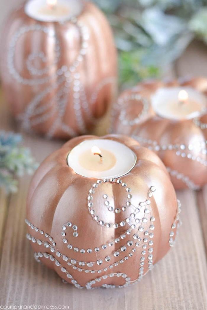 Kerzen in Kürbisse stecken, mit goldenem Spray besprühen, kleine Kristalle kleben