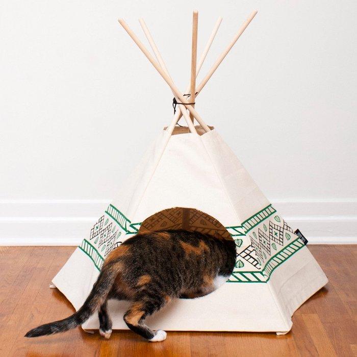eine katze und ein boden aus holz, eine weiße wand und ein kleines mini tipi katzenzelt aus einem weißen stoff und mit langen stöcken aus holz