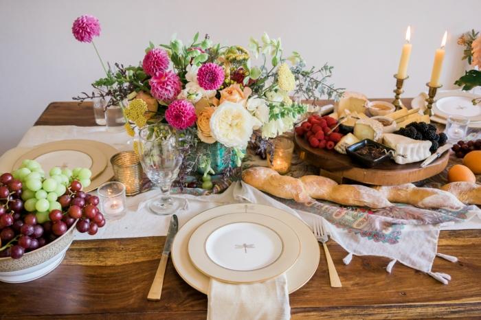 blumengestecke und frische früchte, gebackenes brot, kerzen, alles auf dem tisch schöne idee, tischdeko