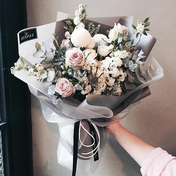 schöne tischdeko, dekoration für die wohnung, eine frau hält einen großen blumenstrauß in grau, rose, weiß