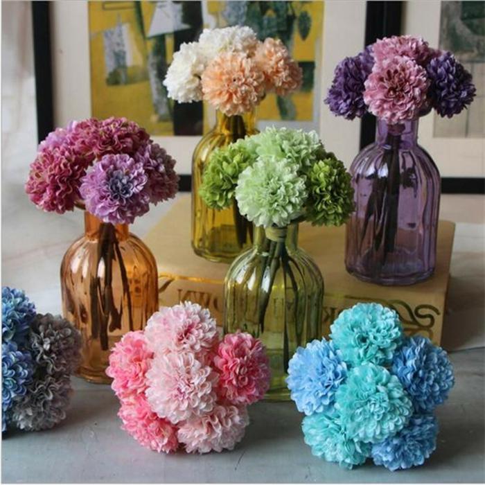 tischdeko blumen, jede blumenfarbe hat die entsprechende farbe der glasflasche die als vase dient, blau, violett, rosa, grün, gelb
