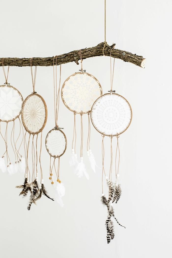 traumfänger basteln, großer ast mit hängenden dreamcatchers, schwarze und weiße federn