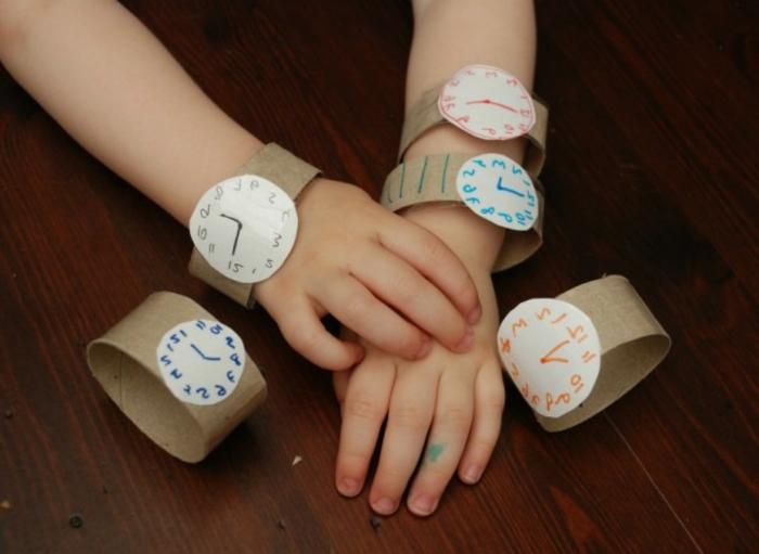 ein Kleinkind mit fünf Armbanduhren, die verschiedene Stunden zeigen, Bastelideen mit Klopapierrollen