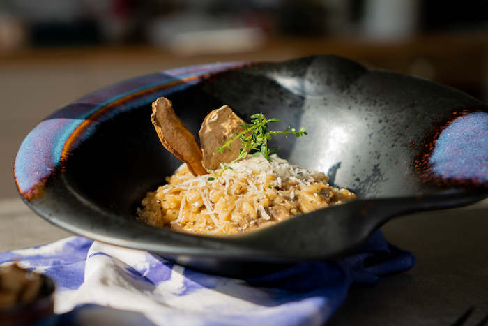 Risotto beim Servieren mit Parmesan, frischem Thymian und Trockenpilzen bestreuen