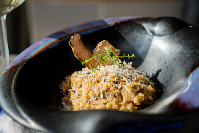 Risotto garnieren mit frischem Thymian, Trockenpilzen und geriebenem Parmesan