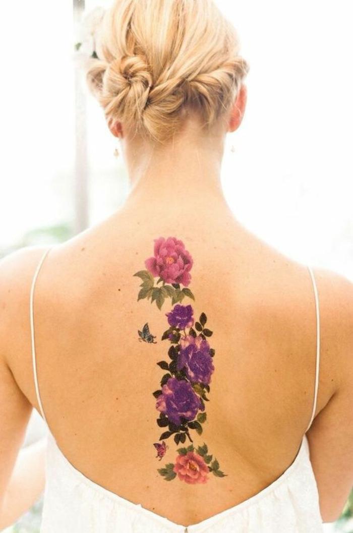 schöne tattooidee, blumen tattoo arm, schulter, rücken, bunte blumen in lila, rosa und grün blonde frau mit schönem haarstyle zu einem besonderen anlass