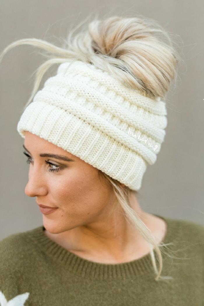 ein blondes Mädchen mit weißer gehäkelten Mütze, Haardutt