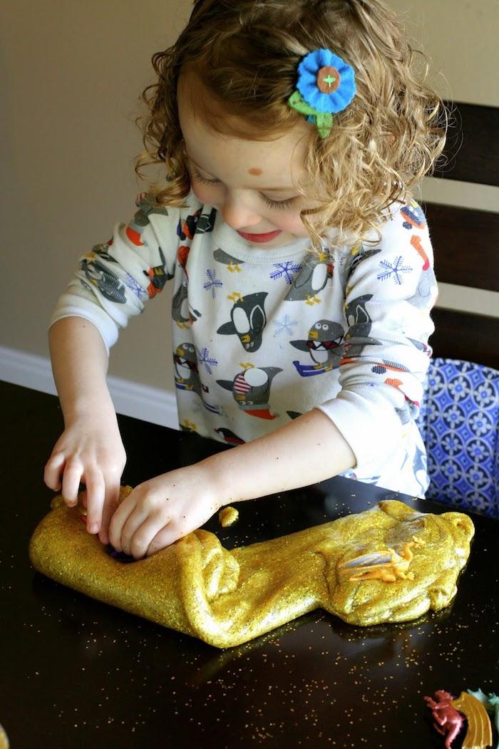Süßes Kind spielt mit Schleim, gelber Slime mit Glitter, Mädchen mit blonden Haare, Bluse mit Pinguinen