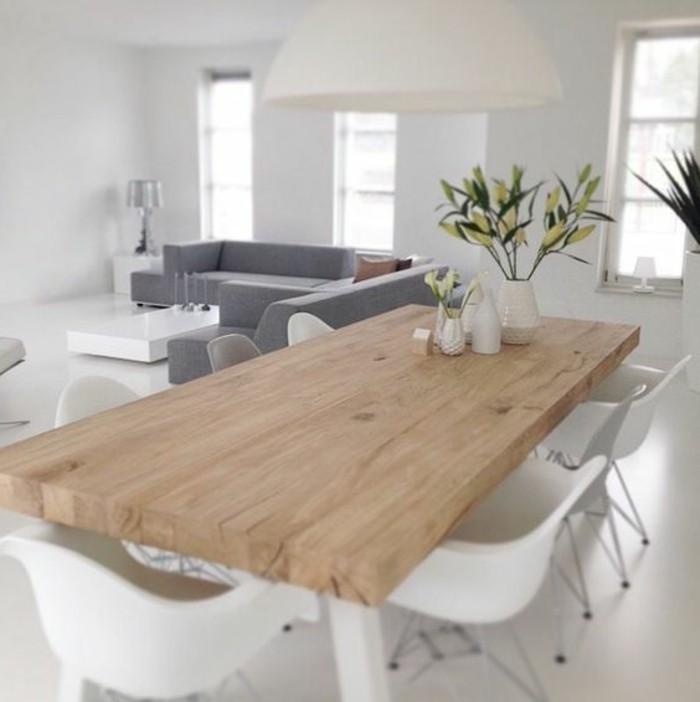 wohn esszimmer mit großem massivholztisch, weiße stühle, blumendeko, ein großes graues sofa daneben