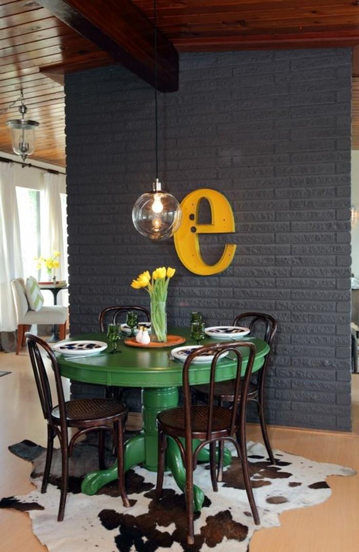 wohn und esszimmer, tischdesign runder tisch in grün lackiert, gelbe tulpen darauf, graue wand streichen