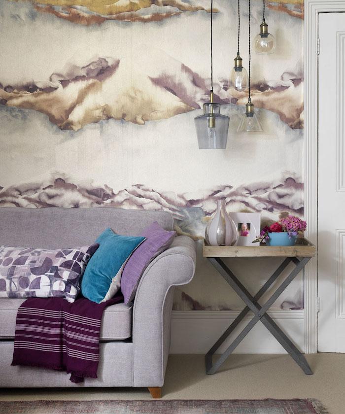 Ein Graues Sofa Mit Blauen Und Violetten Kissen Und Ein Kleiner Tisch Mit  Einer Vase Und
