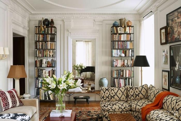 zwei Regale, buntes Sofa, Bilder an den Wänden, weiße Blumen, Einrichtungsideen Wohnzimmer
