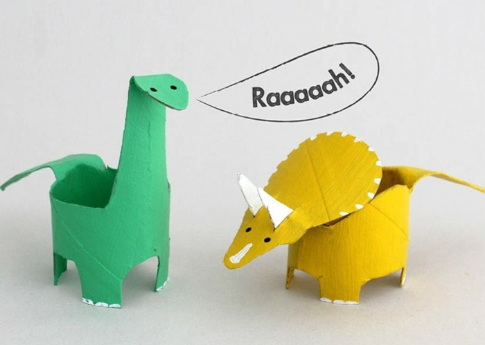 zwei Dinosaurier, einen gelben und einen grünen basteln aus Klopapierrollen