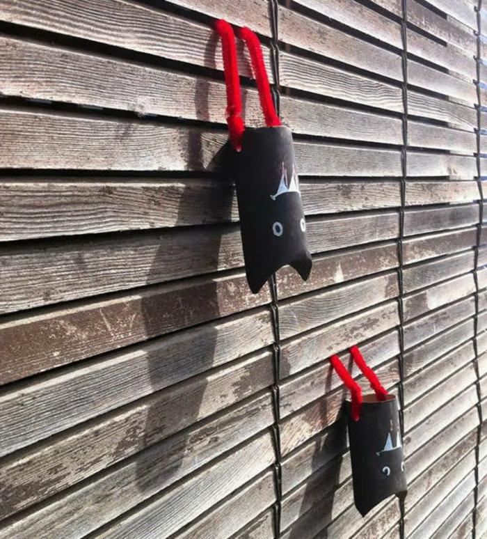 schwarze Fledermäuse mit roten Beinen, ein Zaun aus Dielen, basteln aus Klopapierrollen