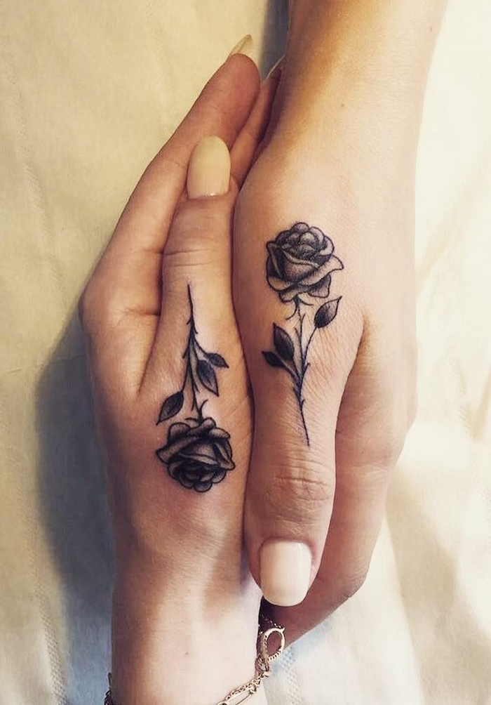 zwei hände mit kleinen schwarzen rosen tattpps mit kleinen schwarzen blättern, eine hand mit einem armband