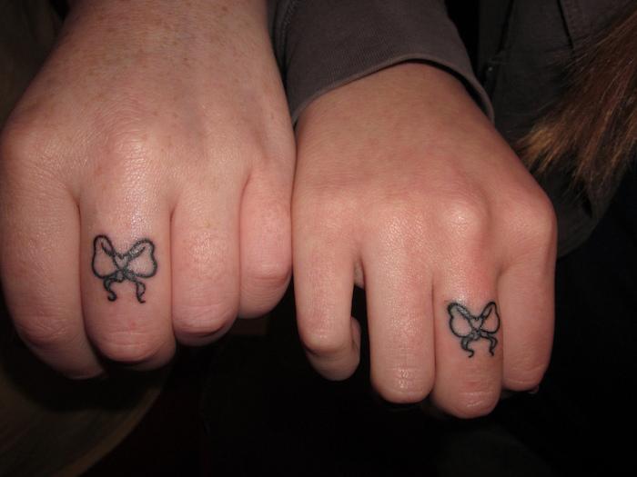 zwei hände mit kleinen schwarzen tattoos mit zwei schwarzen schleifen, tattoos für paare