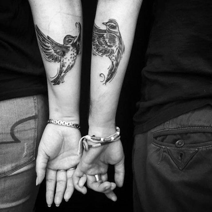 zwei hände mit einem weißen nagellack und mit ringen und armbänder und zwei großen partnertattoos mit fliegenden schwarzen vögeln mit schwarzen federn