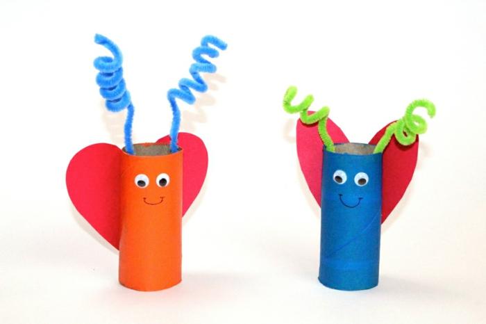 Schmetterlinge in blauer und oranger Farbe mit roten Flügeln, Klopapierrollen basteln mit Kindern