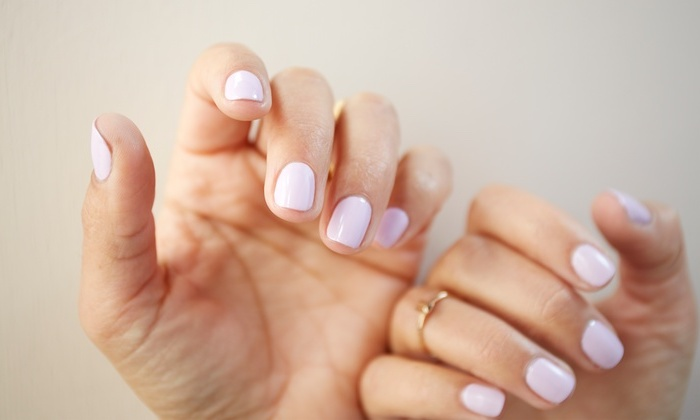gelnägel formen, zwei hände, goldener ring am finger, hellrosa nagellack, kurz