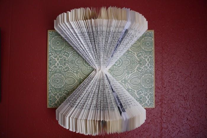 ein bucheinband mit vielen kleinen grünen blumen, ein gefaltetes buch mit einem gelben bucheinband und gefalteten seiten mit schwarzen buchstaben, basteln mit papier ideen, bücher falten diy
