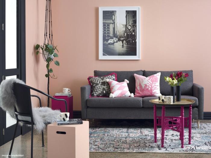 Altrosa Wandfarbe, ein graues Sofa mit rosa Kissen, ein bunter Teppich, ein schönes Bild